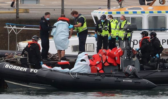 Photo of Migrant pictured waving as he arrives in UK after boats in English Channel intercepted